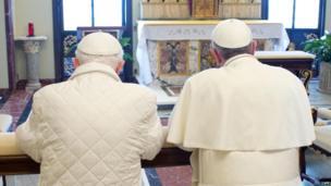 Pope Emeritus Benedict, left, prays with Pope Francis. 23 March 2013