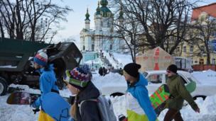 People carry snowboards in Kiev