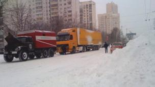 An emergency services tow-truck comes to the aid of a mail lorry on a snow-hit road