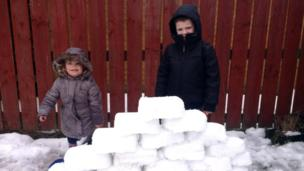 Another brick in the wall ... two children with big plans for an igloo