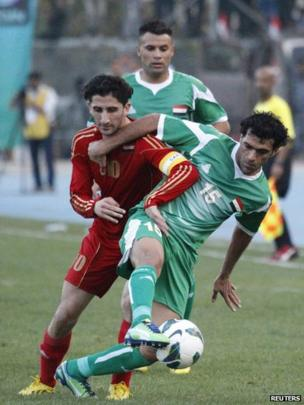 Ali Rehema (L) of Iraq fights for the ball against Sanharib Malki Sabah of Syria during their international friendly football match at Baghdad's Shaab stadium, 26 March