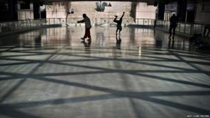 People take advantage of the warm spring-like weather to practice their break-dancing on the Robson Square skating rink in Vancouver