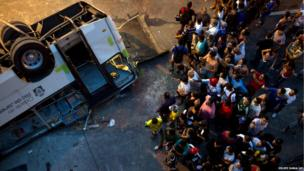 People take pictures of a bus that fell from a viaduct into Avenida Brasil in Rio de Janeiro, Brazil