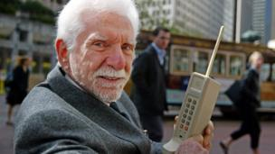 Martin Cooper holding a mobile phone from 40 years ago