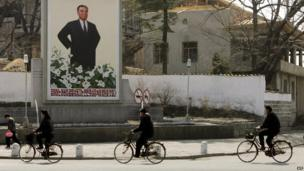 North Koreans ride past a poster of the late leader Kim Il-Sung in the town of Kaesong, 27 March 2005.