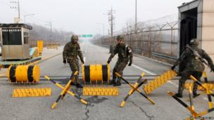 South Korean Army soldiers move barricades to pass vehicles at a military check point in Paju, South Korea, near the border village of Panmunjom