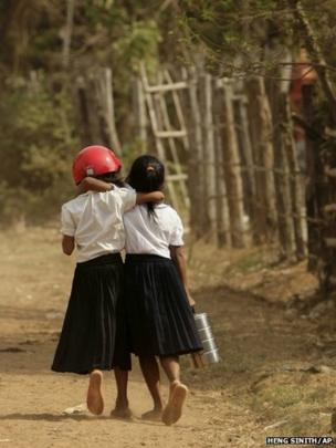 A school girl wears a helmet as she walks home with her friend in Vorsar village, Cambodia