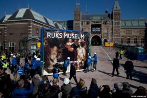 Workers push a crate containing Dutch master Rembrandt's famous Night Watch painting to its new location in the renovated Rijksmuseum in Amsterdam