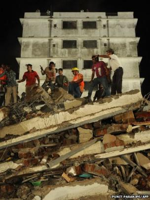 Rescue workers and local residents look for survivors at the site of building collapse near Mumbai