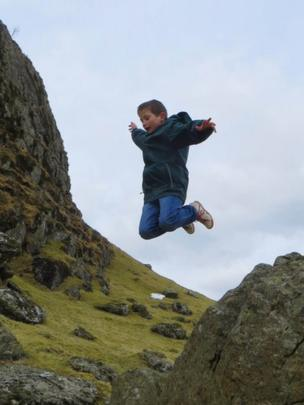Connor jumping off a rock
