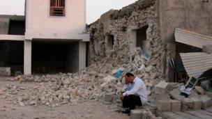An Iranian man sits next to his destroyed house in the town of Shonbeh