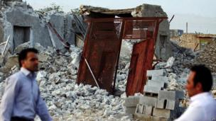 Iranians walk past the ruins of a destroyed house in the town of Shonbeh