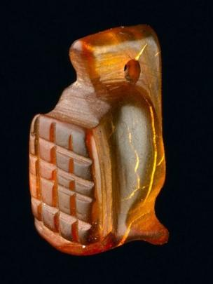 An amber amulet in the shape of a gladiator's helmet