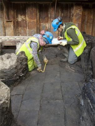 Two archaeologists measuring flagstones