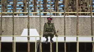 A member of the Kenyan military sits on wooden scaffolding at a stadium in Nairobi on 5 April 2013