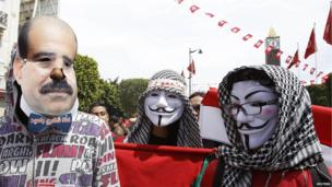Demonstrators wearing Guy Fawkes masks gather on the occasion of the Feast of the Martyrs at Avenue Habib Bourguiba in Tunis - 9 April 2013