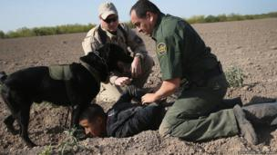 A US Border Patrol canine team works with an US Air and Marine agent to detain an undocumented immigrant