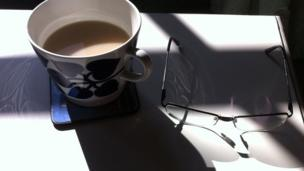 Cup of tea and a pair of glasses