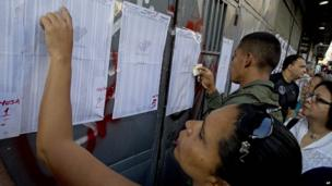 Caracas residents look for their names on the voters' list outside a polling station for voting in presidential elections