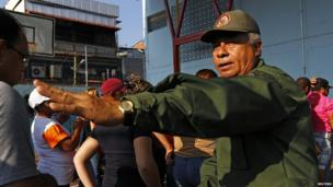 A Venezuelan military officer instructs citizens in Caracas where to line up to vote