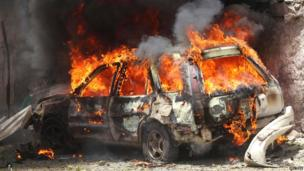 A car goes up in flames outside the main court buildings in Mogadishu