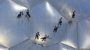 Chinese workers clean the bubble shaped surface of the National Aquatics Center in Beijing