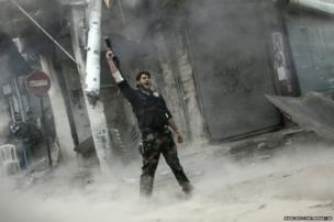 A rebel fighter gestures for victory in Aleppo, Syria, 4 November 2012