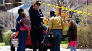 A Boston Police officer lifts the tape for a family to leave flowers in front of the home of the Richard family whose eight-year-old son, Martin, was killed by an explosion near the finish line of the Boston Marathon, 16 April 2013 in Boston, Massachusetts