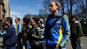 People congregate, including many runners, at a security gate near the scene of yesterday's bombing attack at the Boston Marathon 16 April 2013