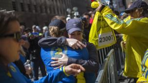 Runners embrace after picking up their medals near the finish line of the Boston Marathon, a day after the race in Boston, Massachusetts on April 16, 2013.