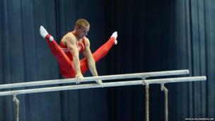 Poland's Adam Kierzkowski competes on the parallel bars