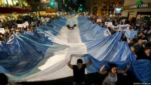 People carry a large Argentine flag during a protest against the government of President Cristina Fernandez in Buenos Aires