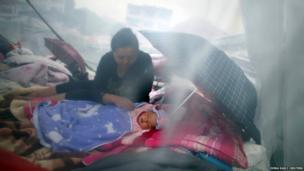 A woman looks at her child as they rest among the wreckage after Saturday's earthquake in Lingguan town
