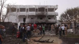 People stand among debris outside the French embassy after the building was attacked, in Tripoli April 23, 2013.