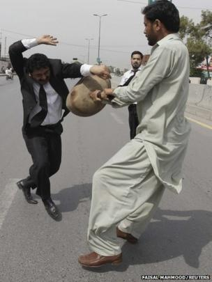 A supporter of Pakistan's former military ruler Pervez Musharraf clashes with an anti-Musharraf lawyer