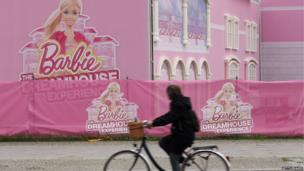 Cyclist rides past the Barbie Dreamhouse Experience in Berlin (23 April 2013)