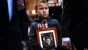 A boy carries a photograph of his deceased grandfather as he marches with veterans during the annual Anzac (Australian and New Zealand Army Corps) Day march in Sydney 25 April 2013