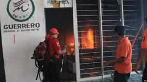Firefighters try to extinguish a fire at the PRI party offices in Chilpancingo