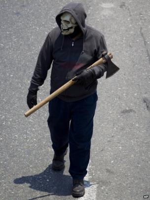 Protester carrying an axe and wearing a skeleton mask marches against education reform on 18 April 2013