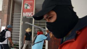 Groups of protesters break the windows of the PRI party's office in Chilpancingo, Guerrero on 24 April 2013