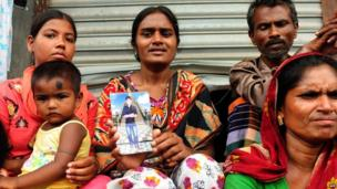 A Bangladeshi woman shows a portrait of her missing brother (25 April 2013)