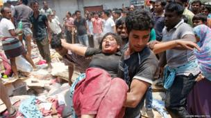People rescue a garment worker who was trapped under the rubble of the collapsed Rana Plaza building in Savar