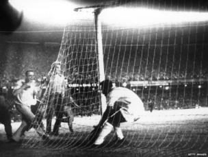 Pele picks the ball from the net after scoring his 1000th goal at the Maracana Stadium. He scored from a penalty for the Brazilian team, Santos, 19 November 1969.