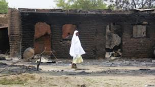 A woman walking past burnt buildings in Baga in Nigeria - Monday 21 April 2013