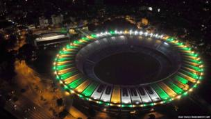 Aerial view of the Maracana stadium emitting light beams of the Brazilian national colours, yellow and green, in Rio de Janeiro on June 16, 2010