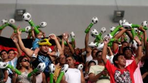 Soccer fans cheer during the re-opening of the newly renovated Maracana Stadium in Rio de Janeiro on Saturday 27 April