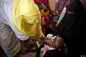 A mother holds her baby while it is vaccinated at Medina Mother and Child Health Centre in Mogadishu, Somalia