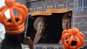 Two girls wearing orange plastic crowds watch the abdication ceremony on a giant screen in Amsterdam on 30 April 2013