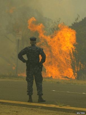 A naval military police officer stands guard as the Springs Fire burns near the Navy SeaBee Training Base in Port Hueneme, California, 3 May