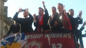 Cardiff players celebrate and one finds the time to take photos as they begin their bus parade to Cardiff Bay.
